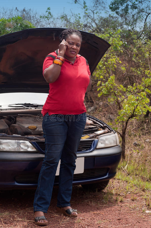 Car breakdown - African American woman call for help, road assistance. African American woman in car breakdown - call for help, road assistance in the tropics royalty free stock photo