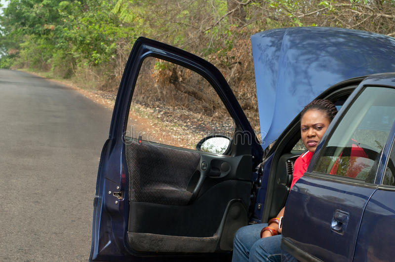 Car breakdown - African American woman wait for he. African American woman in car breakdown - wait for help, road assistance in the tropics stock images