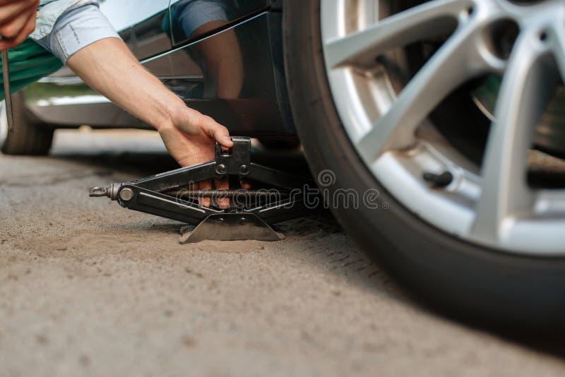 Car breakdown, male person repairing flat tyre royalty free stock photos