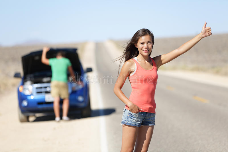 Car breakdown problems - woman hitchhiking. Car breakdown problems - women hitchhiking thumbing while men tries to fix car. Young couple need auto service help stock photos