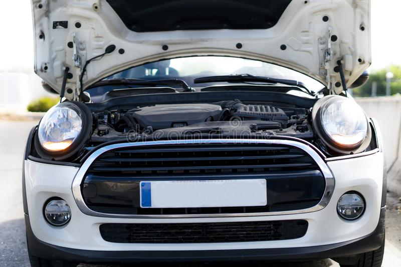 Car with broken engine with the hood open in the middle of the road waiting for technical assistance stock photos