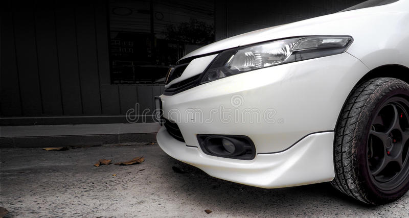 Car Bumper and lamp Side View. White car bumper and lamp side view parking at office, photo high light only red color on the street have dry leaf stock image