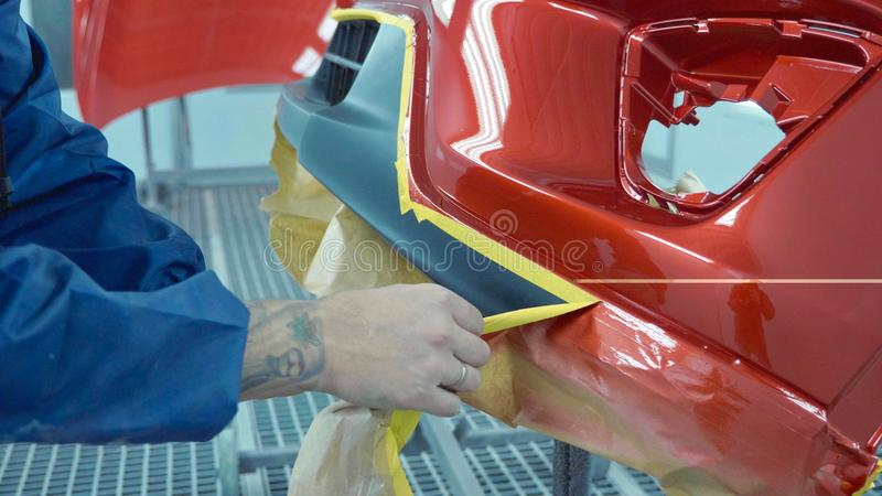 Car bumper after painting in a cars spray booth. Auto vehicle primer bumper. Repairer removes protective film after paint parts. Parts of car in cars spray stock photo