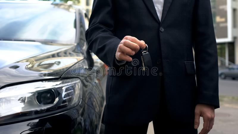 Car buyer holding keys to new vehicle, successful auto purchase transaction. Stock photo stock photo