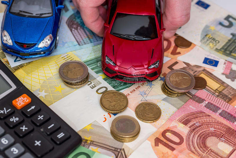 Car and calculator, money, pen. Toy car, euro ntoes, calculator royalty free stock photography
