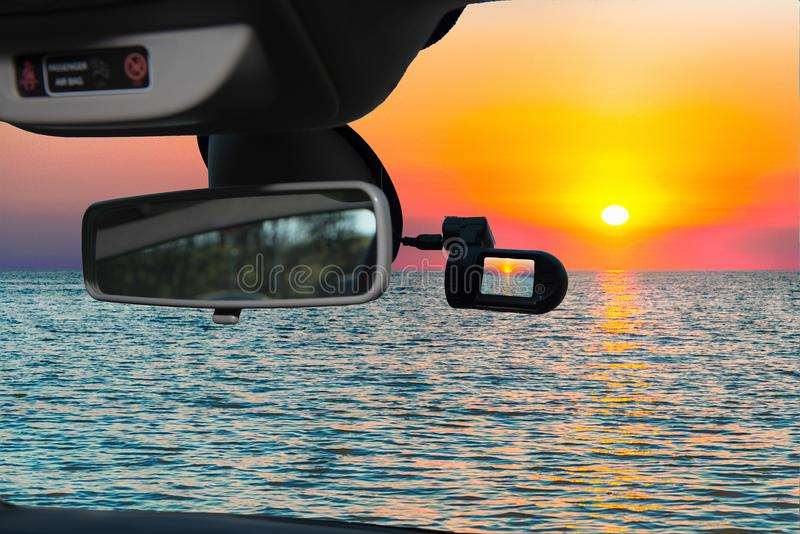 Car camera view of scenic sunset on the mediterranean sea. Looking through a dashcam car camera installed on a windshield with view of a scenic sunset on the stock photo