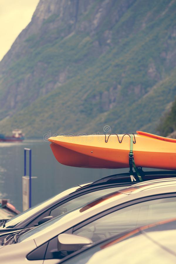 Car with canoes on top. Active lifestyle sport concept. Car with kayak yellow canoe on top roof ready to transportation stock photo