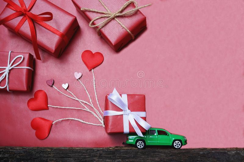 Car carrying red lovely gift box pulling red heart figure on red background, sweet valentine present delivery concept. Copy space royalty free stock image