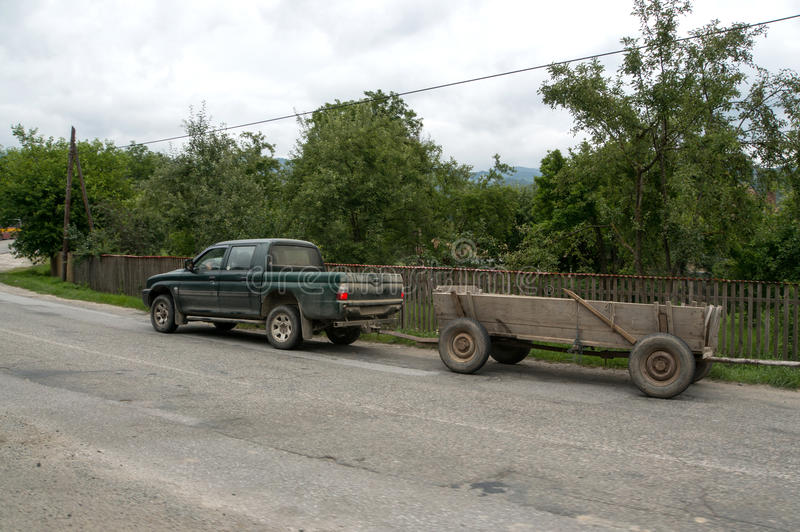 Car with cart. A 4x4 vehicle towing a cart in a village in Romania royalty free stock photo