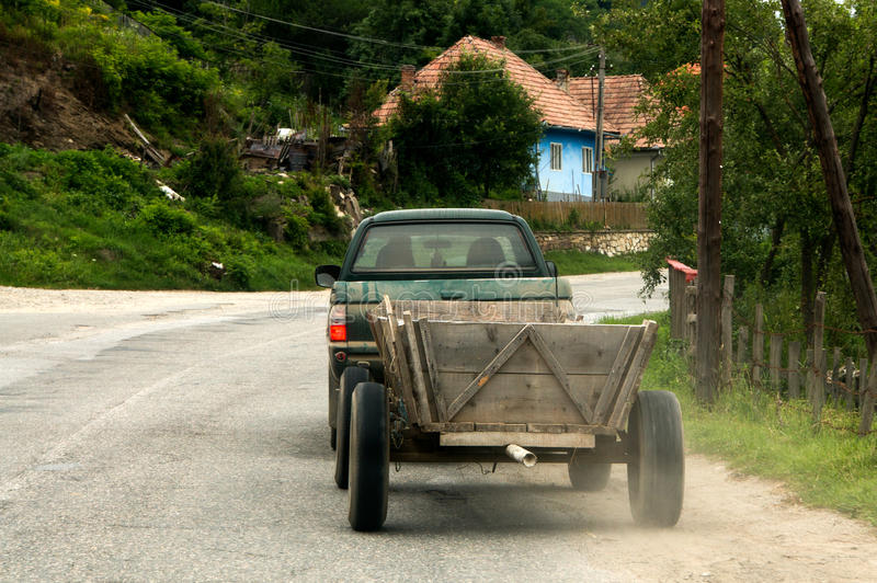Car with cart. A 4x4 vehicle towing a cart in a village in Romania stock image