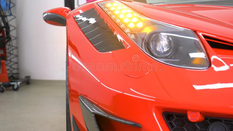 In the car center in the garage, professionals polish a new sports car. Luxury car polishing. Concept of: Racing, Sport car, New. Slow motion, Nascar, Red royalty free stock images