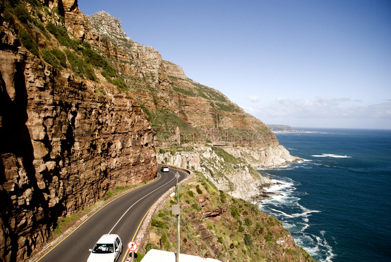 Car on Chapmans Peak Drive Landscape. Chapmans Peak Drive with Kommetjie in the distance. Motor vehicles on the road royalty free stock images
