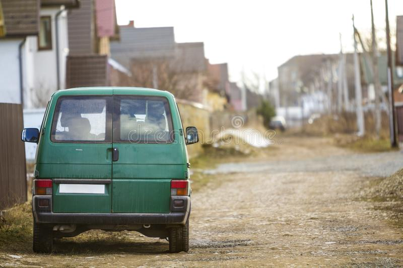 Car on the city street. Green minibus parked at the side of the road. Car on the city street. Green minibus parked at the side of the road stock photography