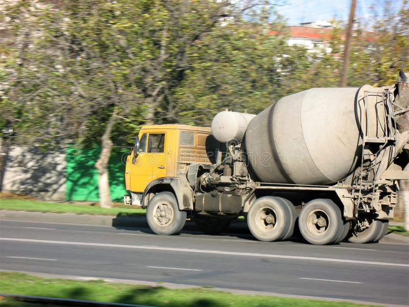 Car concrete mixer yellow rides on the road. Car yellow concrete mixer rides on the road for delivery of cargo at the destination stock images