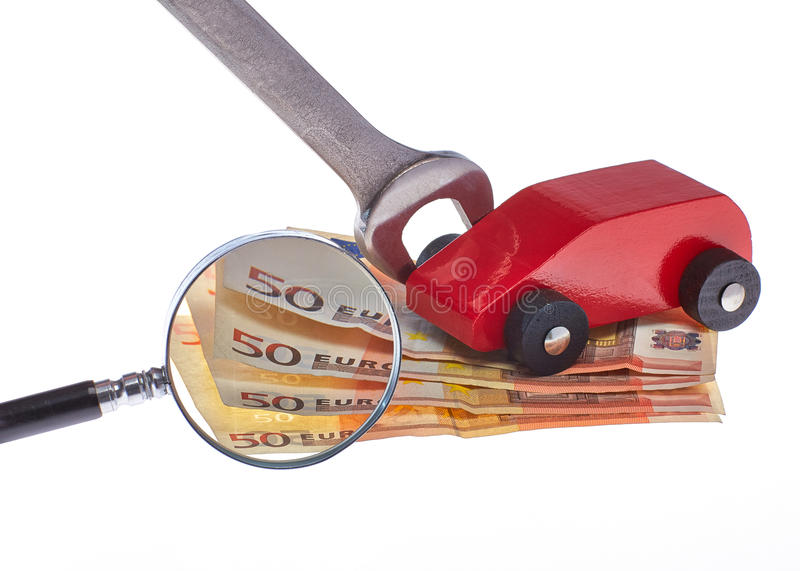 Car costs. Symbolizes for review by money and toy car is the enlarged with a magnifying glass stock photo
