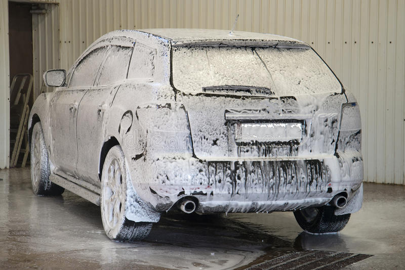 The car is covered with the foam at the car wash royalty free stock photos