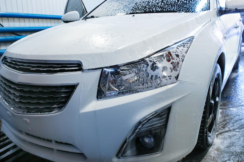 Car covered with foam in car wash royalty free stock images