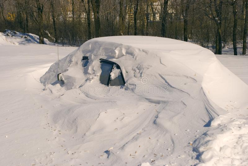 Car covered with snow in winter blizzard snowdrift royalty free stock photos