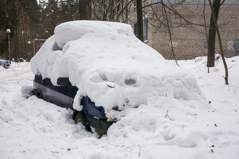 The car, covered with thick layer of snow, in the yard of residential house in provilcial town. Negative impact of heavy snowfall. Yards and surrounding stock images