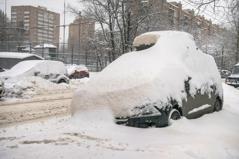 The car, covered with thick layer of snow, in the yard of residential house in provilcial town. Negative impact of heavy snowfall. Yards and surrounding royalty free stock photo