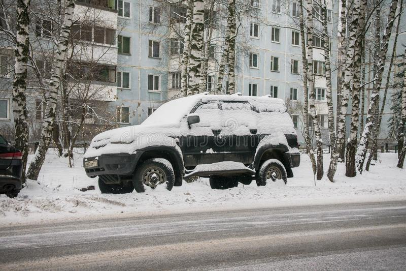 The car, covered with thick layer of snow, in the yard of residential house in provilcial town. Negative impact of heavy snowfall. Yards and surrounding royalty free stock photos