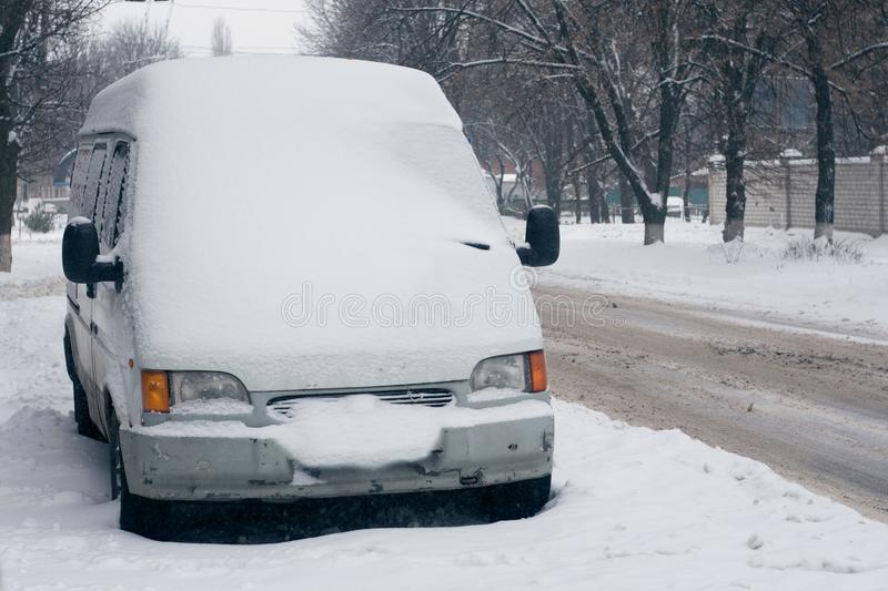 Car covered with white snow in the city. Minibus under the snow. Sleet slush, ice covering on the roads, and southeastern royalty free stock image