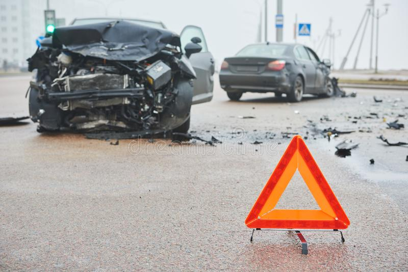 Accident or crash with two automobile. Road warning triangle sign in focus. Car crash in city street. Accident with two automobile. Road warning triangle sign in royalty free stock image