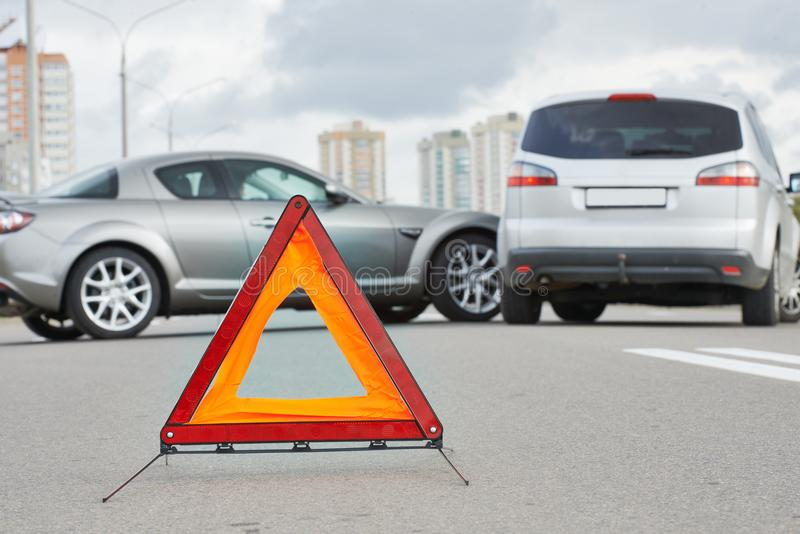 Accident or crash with two automobile. Road warning triangle sign in focus. Car crash in city street. Accident with two automobile. Road warning triangle sign in stock images