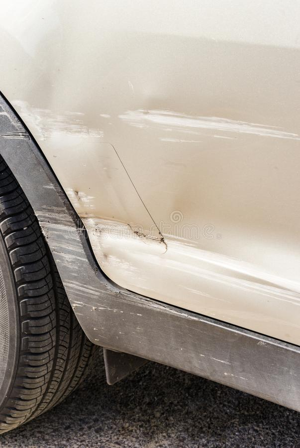 Car crash, close-up of scratched and damaged silver car door royalty free stock images