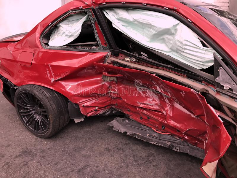 Car Crash Damage. Extensive car accident damage on the passenger side of a red sedan stock photos