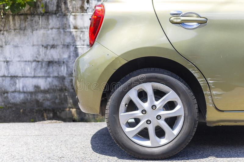 Car crash. Beside the deep green color car have scratch from damage on road. Close up scratch stock image