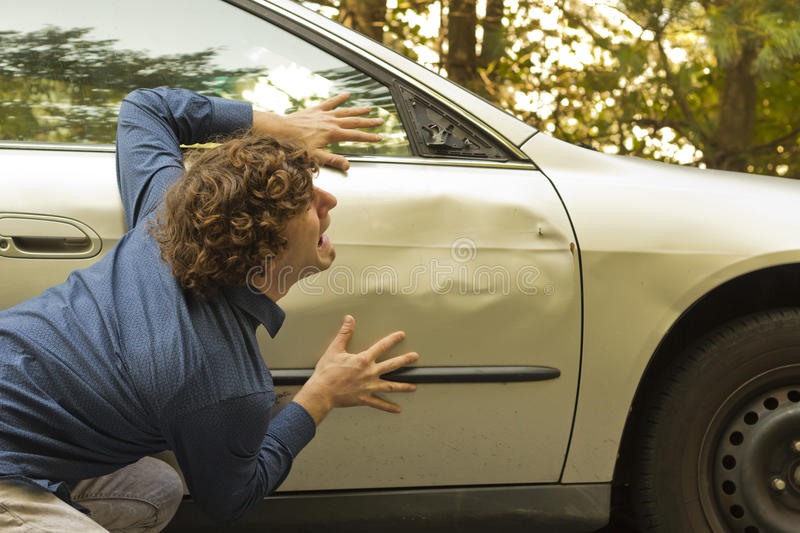 Car Crash Facial Expression. Silly man makes angry annoyed facial expression about dame to his car stock image