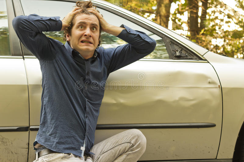 Car Crash Facial Expression. Silly man makes angry annoyed facial expression about dame to his car royalty free stock photography