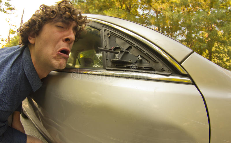Car Crash Facial Expression. Silly man makes angry annoyed facial expression about dame to his car royalty free stock photos