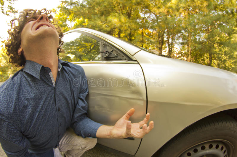 Car Crash Facial Expression. Silly man makes angry annoyed facial expression about dame to his car stock photography