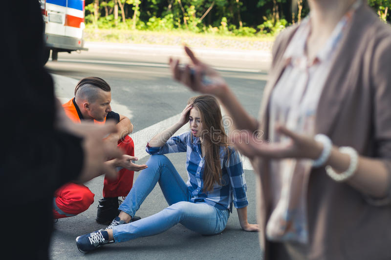 Car crash victim with paramedic helping her. Young victim of car crash sitting on a road with paramedic helping her royalty free stock photos