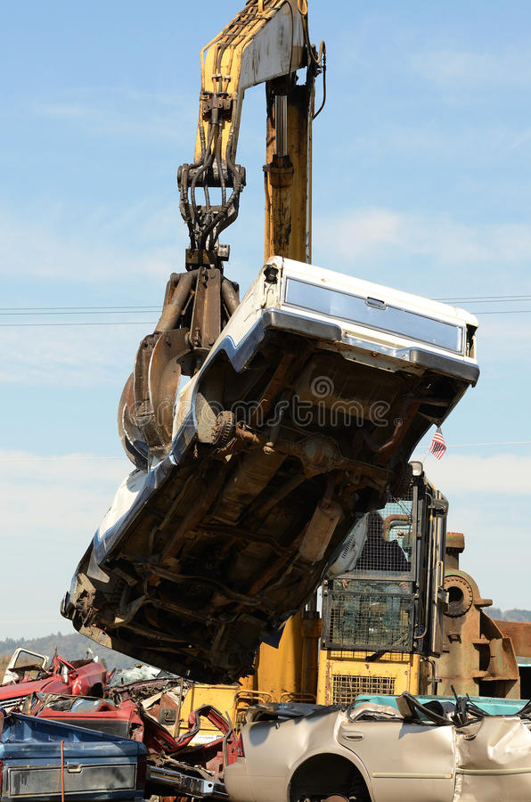 Car Crush. Large excavator with a claw crushing and piling old cars at a metal recycle plant stock photo
