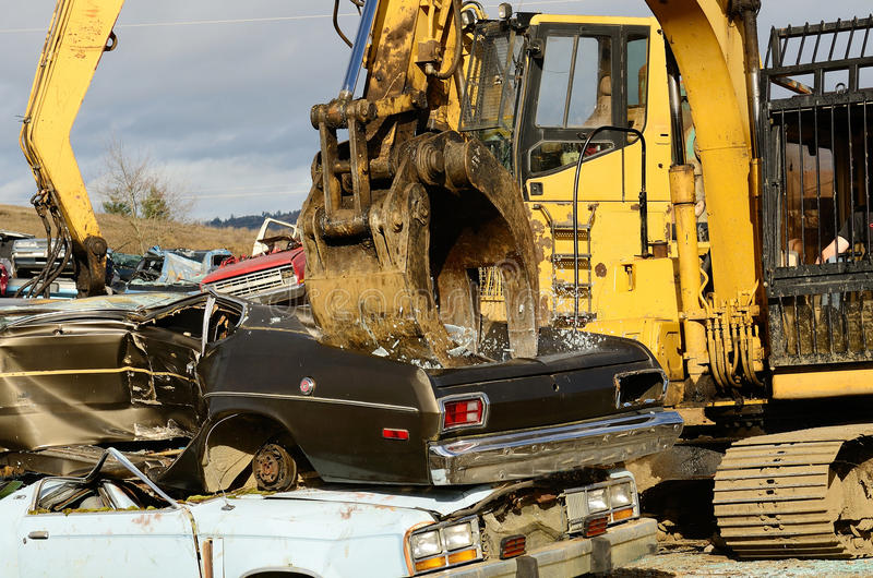 Car Crush. A large excavator crushing and piling discarded autos for metal recyling stock image