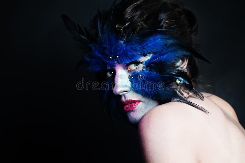 Car?cter de Halloween Mujer modelo con maquillaje azul del p?jaro en fondo negro imagenes de archivo