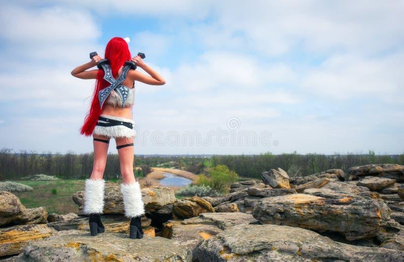 Car?cter femenino hermoso con dos espadas en ?rea de monta?a Modelo de moda Girl fotografía de archivo