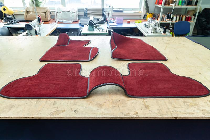Car 3D handmade floor mats of red color from wool for front and rear passengers of a vehicle in an interior design workshop with royalty free stock photography