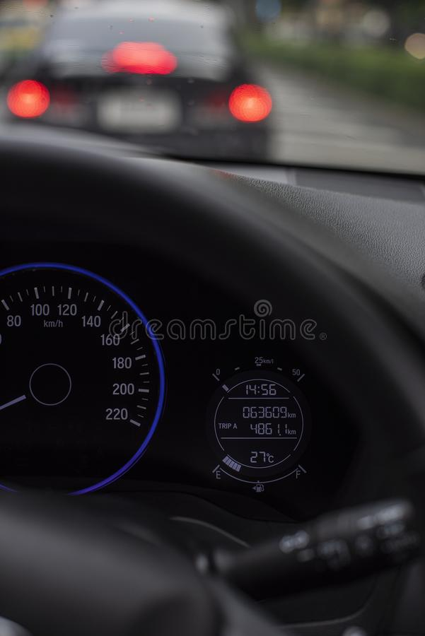 Car dashboard or console panel with Illuminated digital miles screen including gauges telling fuel, battery and lighting system. royalty free stock photography