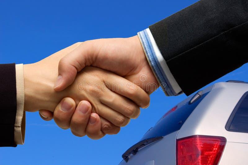 Car Deal. Asian woman and Caucasian man shaking hands
