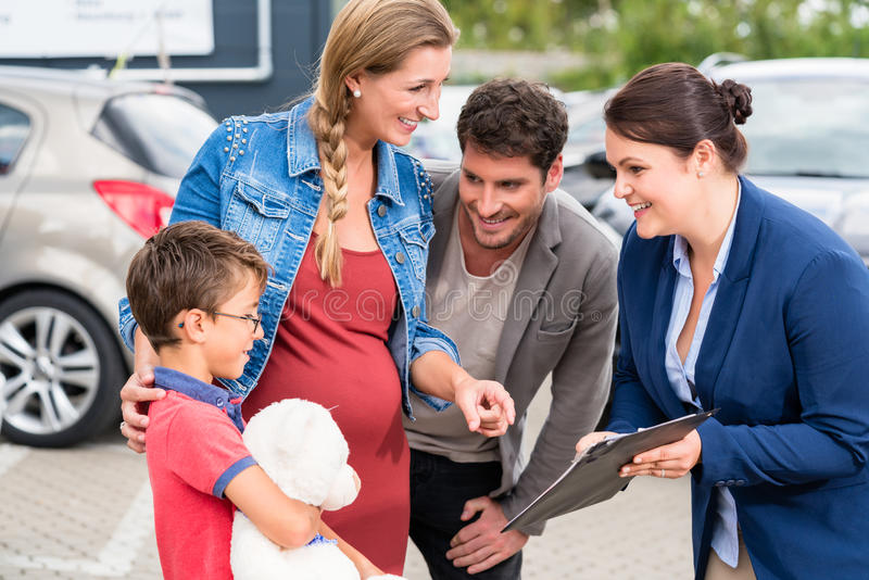 Car dealer advising family on buying auto. Showing price list royalty free stock photos