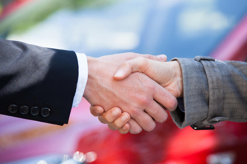 Car dealer and female client shaking hands at dealership. Cropped image of car dealer and female client shaking hands at dealership royalty free stock photos