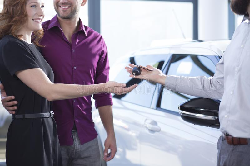 Car dealer giving keys to happy woman and smiling man in a dealing salon stock photos
