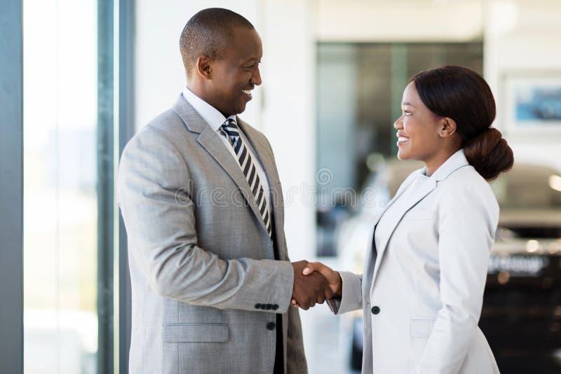 Car dealer handshake customer. Cheerful african car dealer handshake with customer in showroom royalty free stock photos