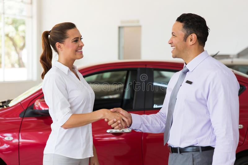 Car dealer handshake customer. Cheerful middle aged car dealer handshake with customer in showroom stock photography