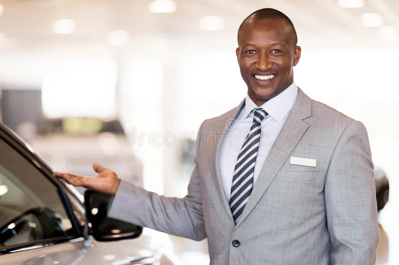 Car dealer presenting. Friendly african car dealer presenting new vehicle in showroom royalty free stock photos