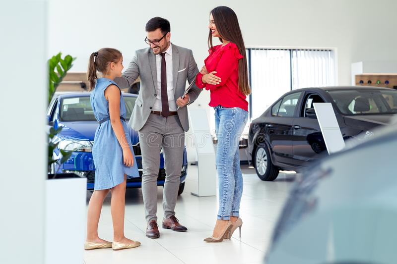 Car dealer selling new vehicle to beautiful young family royalty free stock image